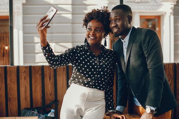 Um jovem e elegante casal de pele escura em pé em uma cidade ensolarada