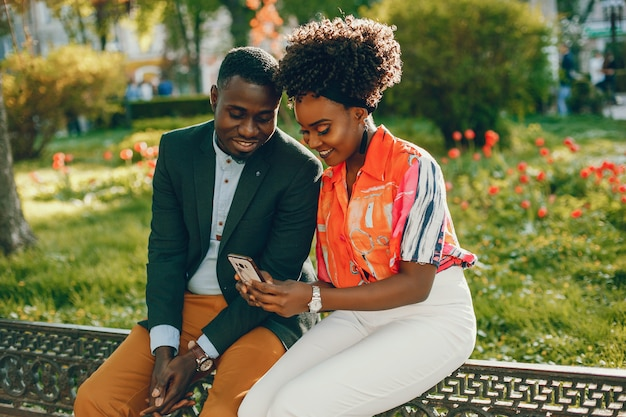 Um jovem e elegante casal de pele escura, sentado em uma cidade ensolarada e usar o telefone
