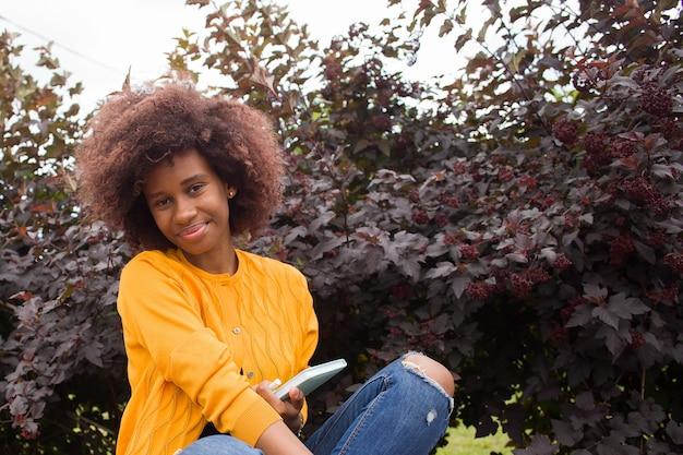 Um jovem e feliz estudante afro-americano no parque
