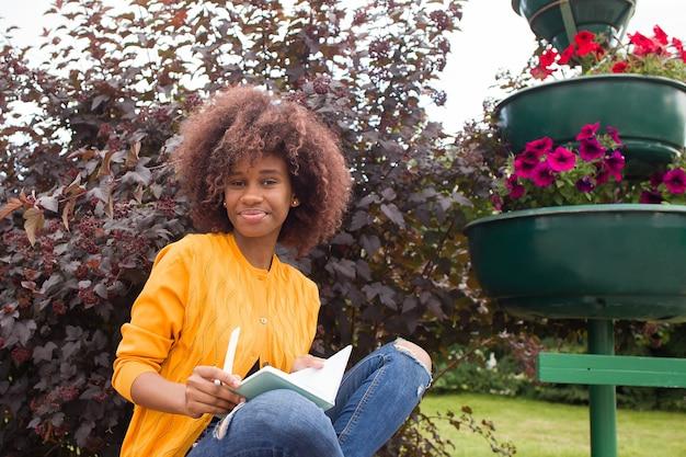 Um jovem e feliz estudante no parque