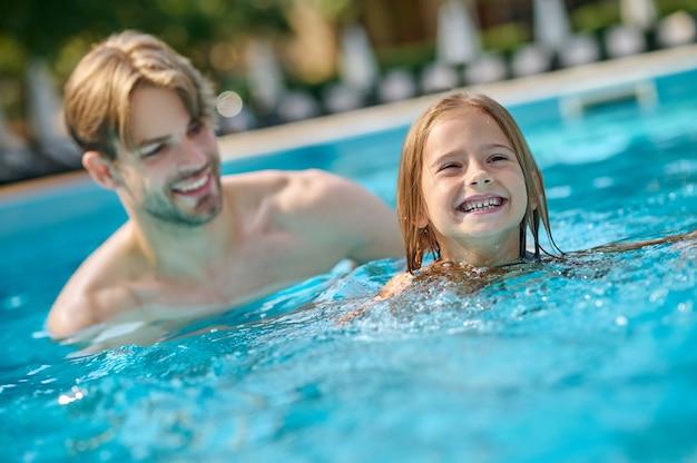 Um jovem e seu filho nadando na piscina e parecendo se divertir