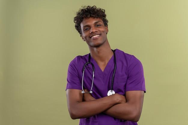 Um jovem e sorridente médico bonito de pele escura com cabelo encaracolado, usando uniforme violeta com estetoscópio de mãos postas enquanto em um espaço verde