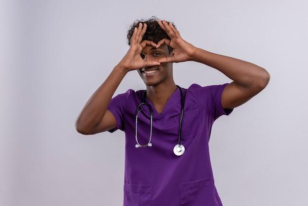Um jovem e sorridente médico de pele escura com cabelo encaracolado, usando uniforme violeta com estetoscópio mostrando o sinal do formato do coração com os dedos