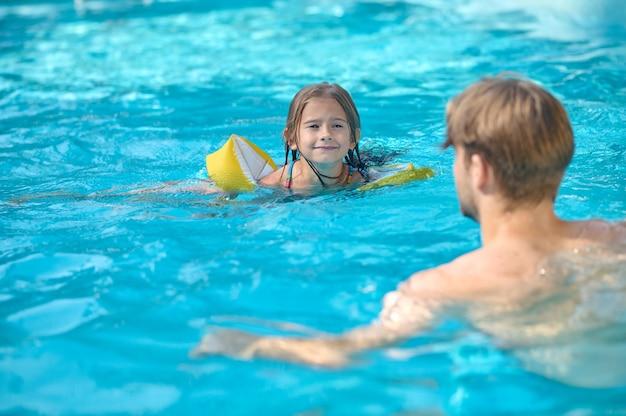 Um jovem e sua filha nadando na piscina e parecendo se divertir