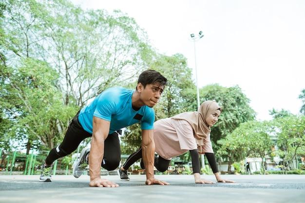 Um jovem e uma garota com um lenço na cabeça fazendo movimentos musculares abdominais juntos durante exercícios ao ar livre no parque