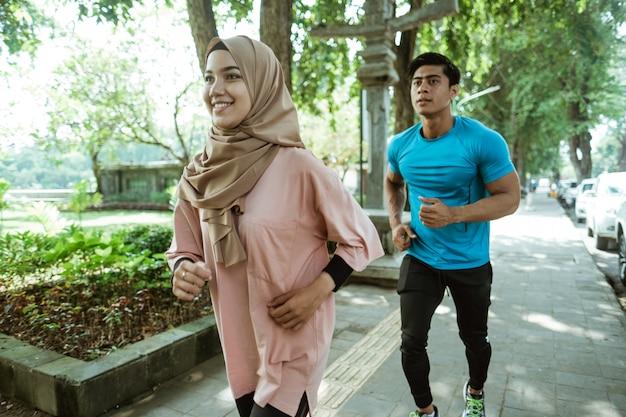 Um jovem e uma menina com um lenço na cabeça fazendo jogging juntos durante exercícios ao ar livre no parque