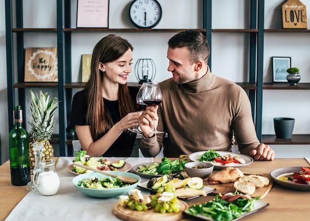 Um jovem e uma mulher estão sentados a uma mesa coberta com comidas e bebidas com taças de vinho nas mãos