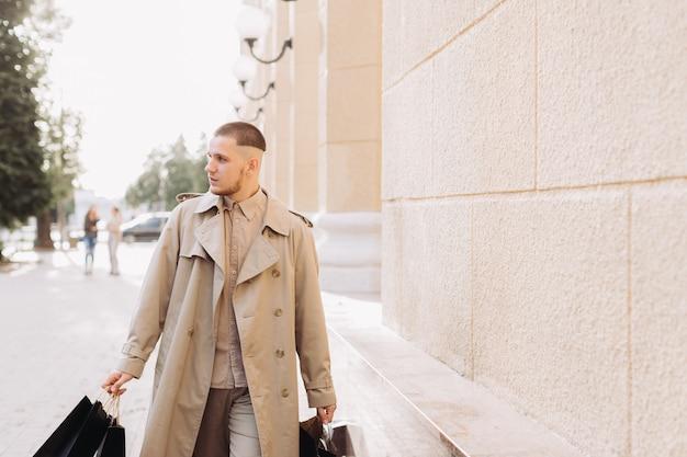 Um jovem elegante com sacos depois de fazer compras bem sucedidas na black friday