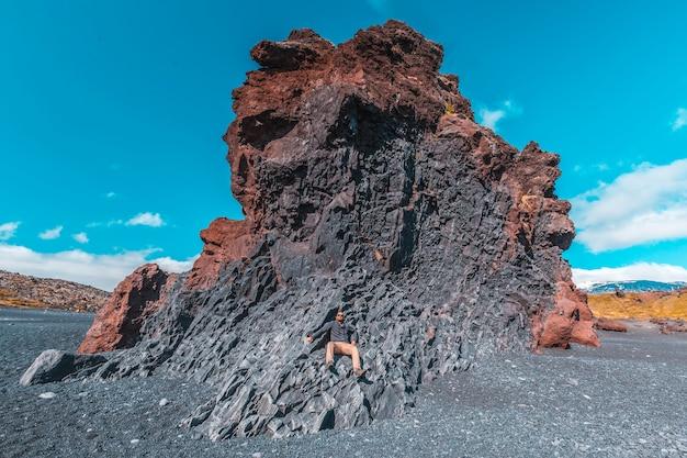 Um jovem em cima de algumas pedras, sentado na praia negra da costa de snaefellsnes. islândia