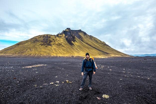 Um jovem em cinzas vulcânicas e uma montanha verde. landmannalaugar, islândia