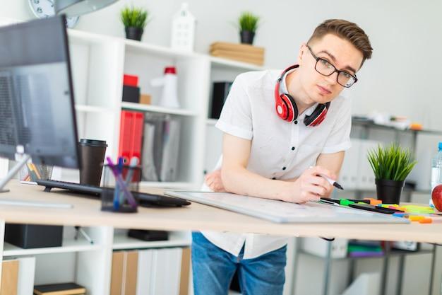 Um jovem em copos fica perto de uma mesa de computador. um jovem desenha um marcador em um quadro magnético. no pescoço, os fones de ouvido do cara estão pendurados.