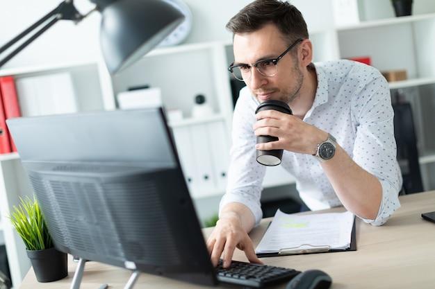 Um jovem em copos fica perto de uma mesa no escritório, detém um copo de café na mão e trabalha com um computador