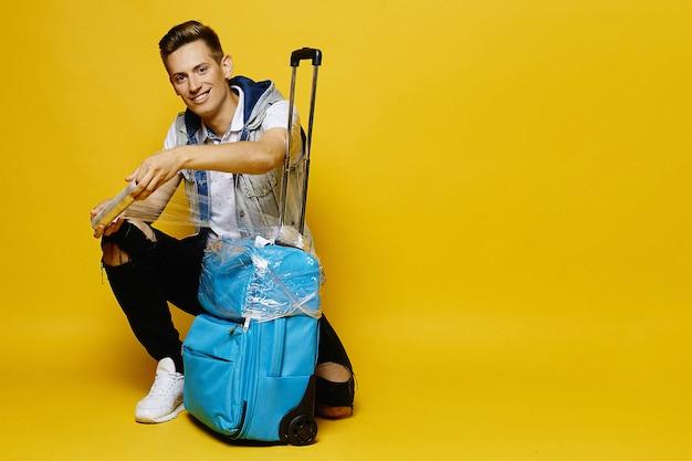 Um jovem em roupas jeans está preparando sua mala de viagem para entregá-la na bagagem, isolada na parede amarela.