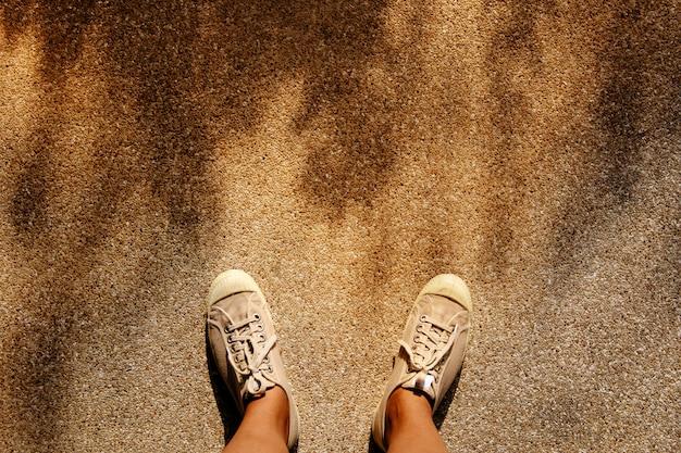 Um jovem em sapatos de tênis de pé contra a luz do sol quente.
