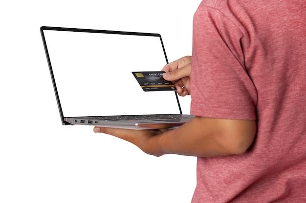 Um jovem em t-shirt casual vestindo segurando um laptop e um cartão de crédito usando, trabalhando online.