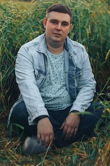 Um jovem em um campo com trigo verde