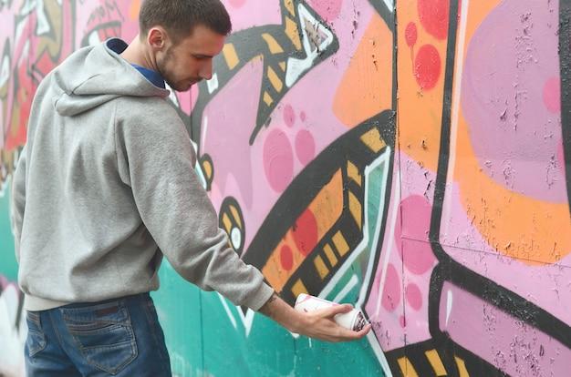 Um jovem em um capuz cinza pinta graffiti em rosa e verde