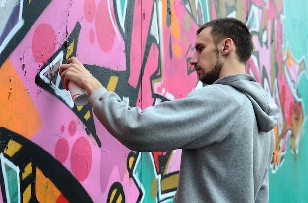 Um jovem em um capuz cinza pinta graffiti em rosa