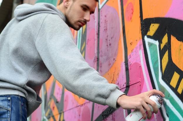 Um jovem em um capuz cinza pinta graffiti