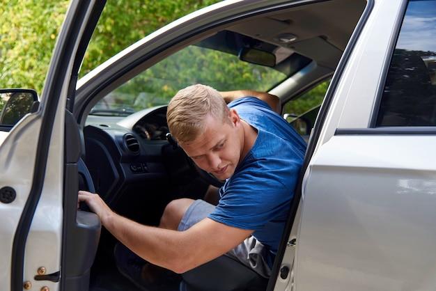 Um jovem em um carro com uma porta aberta e olha para trás.