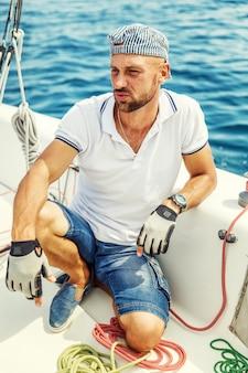 Um jovem em um iate no mar