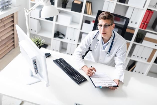 Um jovem em um manto branco sentado em uma mesa no escritório ele detém uma caneta na mão e olha em linha reta