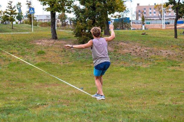 Um jovem em um parque público aprendendo a andar na corda bamba