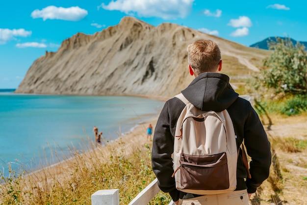 Um jovem em uma área de estilo rústico perto de uma cerca branca e uma vista da montanha no cabo camaleão