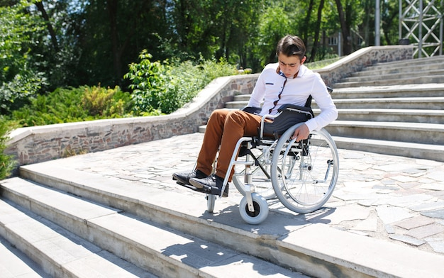 Um jovem em uma cadeira de rodas que não pode descer as escadas.