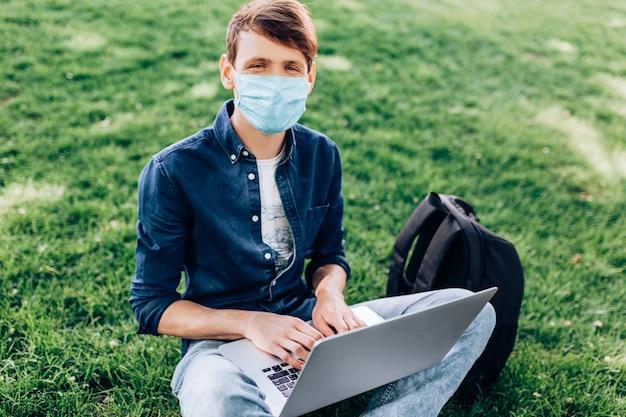 Um jovem em uma máscara médica protetora no rosto, sentado na grama em um parque com um laptop