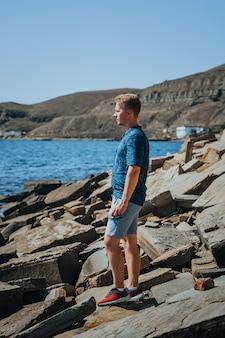 Um jovem em uma praia rochosa feita de pedras naturais na crimeia