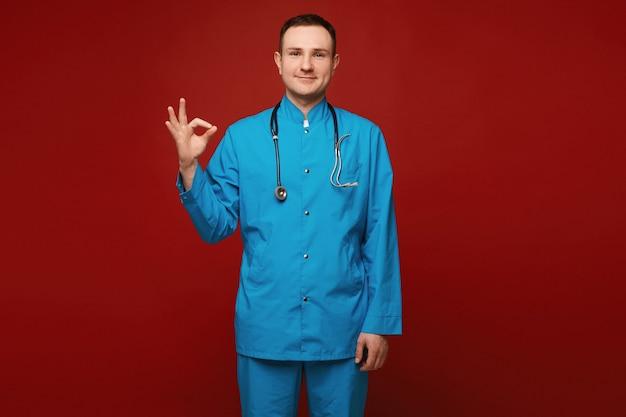 Um jovem em uniforme médico e com um estetoscópio mostrando gesto de ok e posando em vermelho
