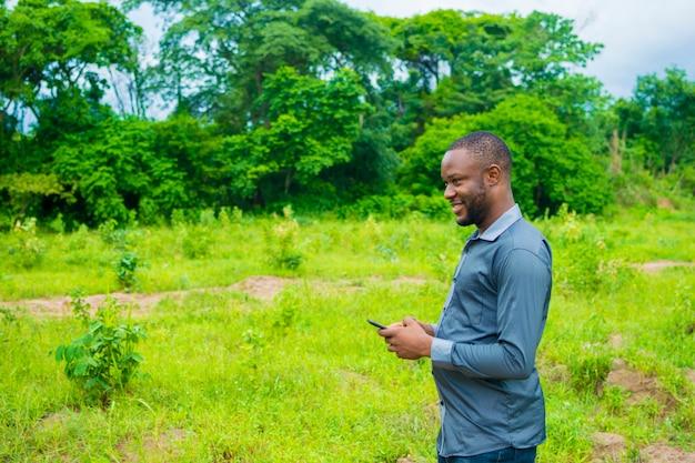 Um jovem empresário africano bonito se sentindo animado com o que viu em seu celular.