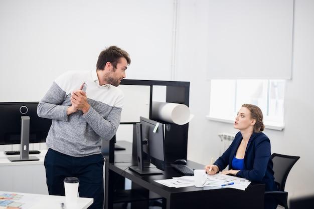 Um jovem empresário aprendendo algumas informações com seu colega para fornecer uma resposta imediata ao cliente