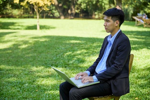 Um jovem empresário asiático sentado no jardim a trabalhar