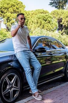 Um jovem empresário asiático, um homem de óculos escuros, está perto de um carro moderno e fala ao celular, solucionando problemas e perguntas