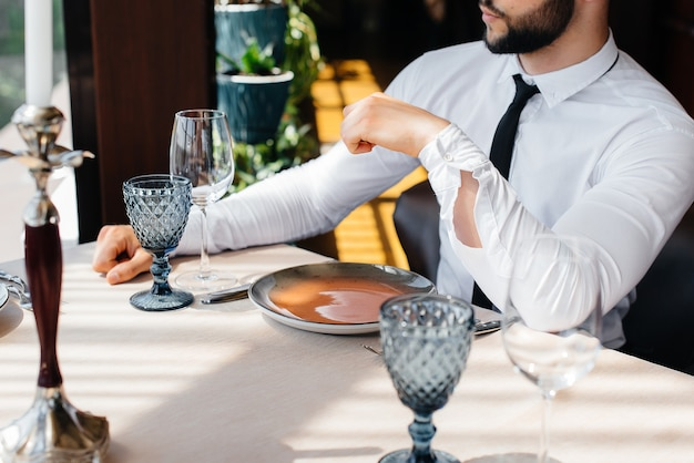 Um jovem empresário barbudo está sentado à mesa em um restaurante fino e esperando seu pedido. atendimento ao cliente na área de catering.