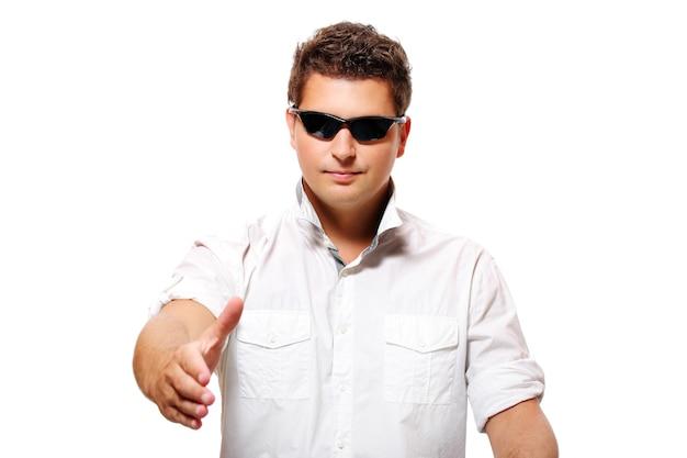 Um jovem empresário bonito apertando as mãos sobre fundo branco