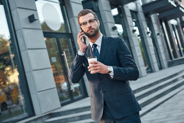 Um jovem empresário bonito de óculos está falando ao telefone e bebendo café