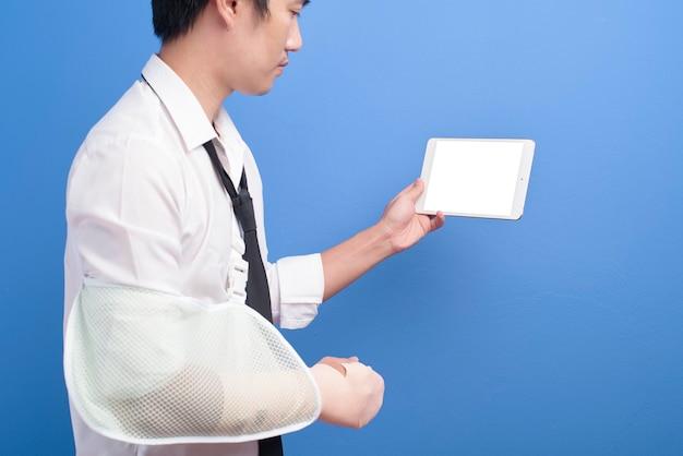 Um jovem empresário com um braço ferido em uma tipóia usando um tablet sobre uma parede azul, seguro e conceito de saúde