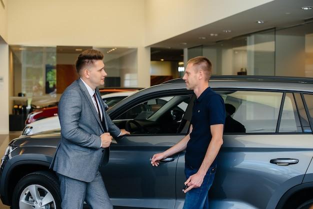 Um jovem empresário com um vendedor olha para um carro novo em uma concessionária. comprando um carro.