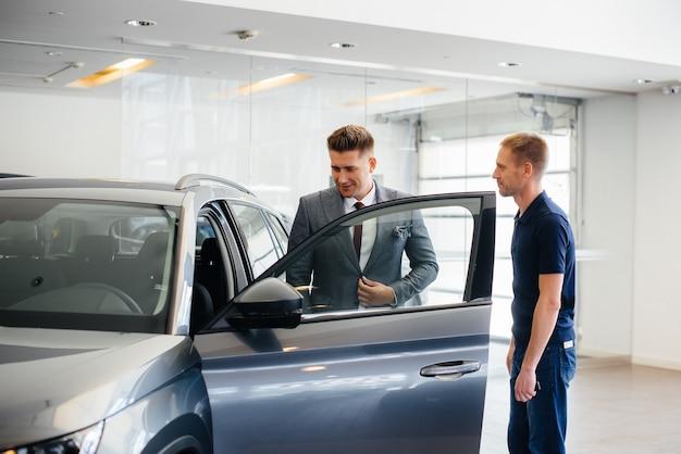 Um jovem empresário com um vendedor olha um carro novo em uma concessionária
