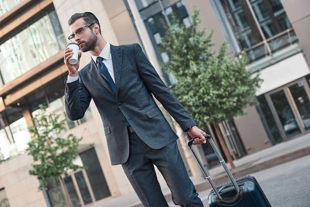 Um jovem empresário de óculos atravessa a estrada com café e mala.