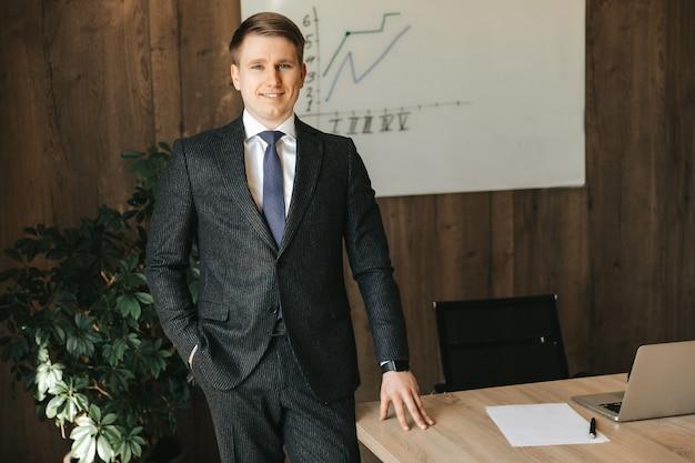 Um jovem empresário de sucesso está usando um terno clássico no escritório.