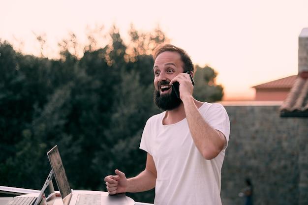 Um jovem empresário em uma reunião por telefone enquanto trabalhava com seu tablet em sua casa na floresta