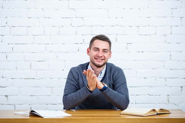 Um jovem empresário está sentado a uma mesa com um livro