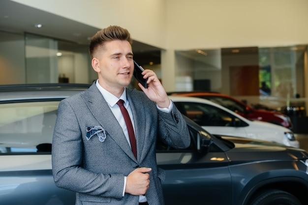 Um jovem empresário faz uma ligação após comprar um carro novo.