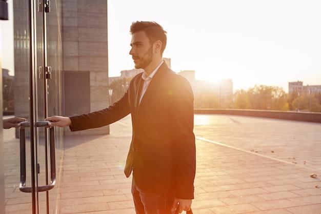 Um jovem empresário masculino em um terno elegante e uma camisa branca com uma grande bolsa preta