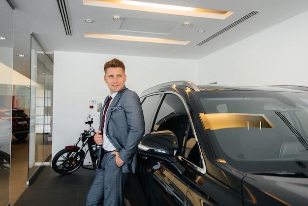 Um jovem empresário olha um carro novo em uma concessionária