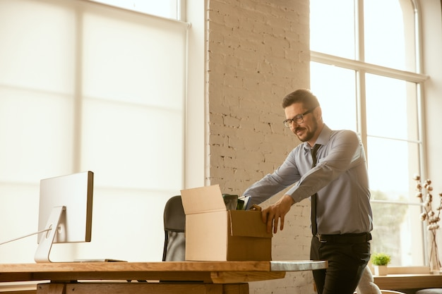Um jovem empresário se mudando no escritório, conseguindo um novo local de trabalho. jovem trabalhador de escritório do sexo masculino, caucasiano, equipa o novo gabinete após a promoção. parece feliz. negócios, estilo de vida, novo conceito de vida.